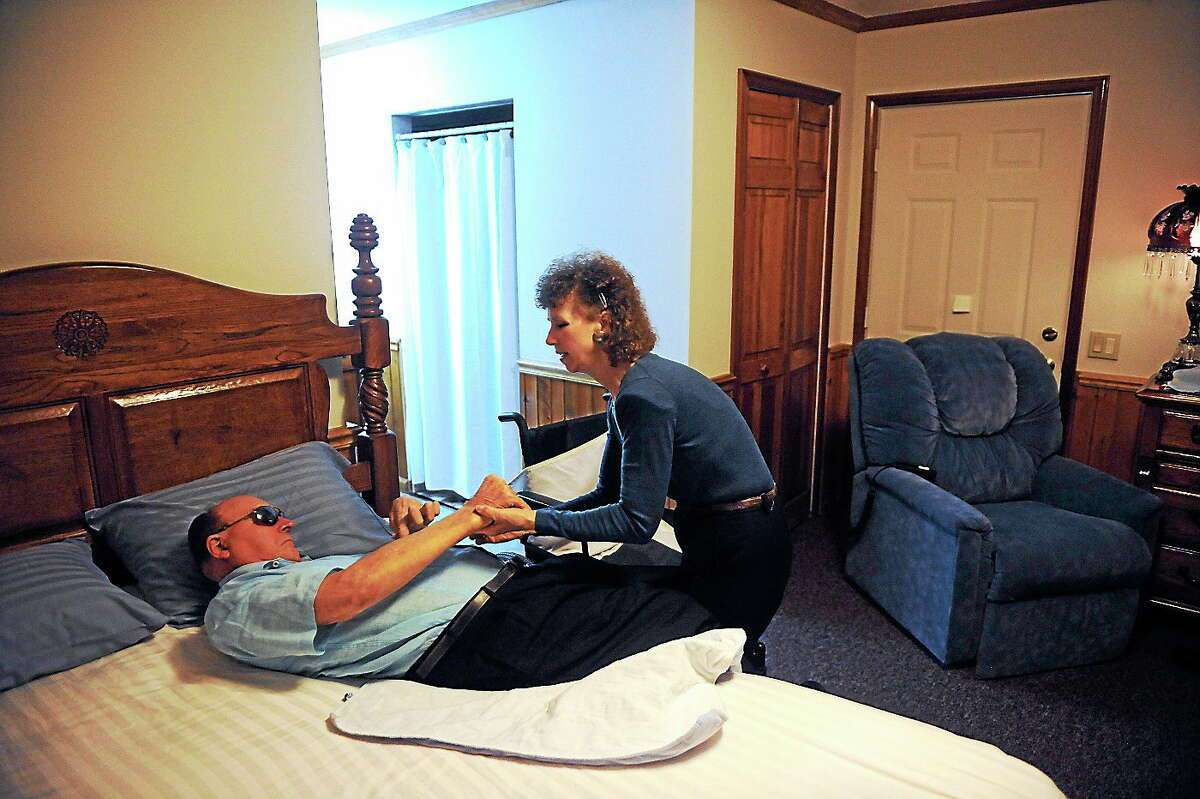 In this Aug. 30, 2013 photo, Pauline King cares for her husband Jerry King at their home in Anna, Ill. Jerry was diagnosed with Multiple Sclerosis in 1978. He can no longer go to the bathroom, bathe or dress himself without assistance from Pauline.