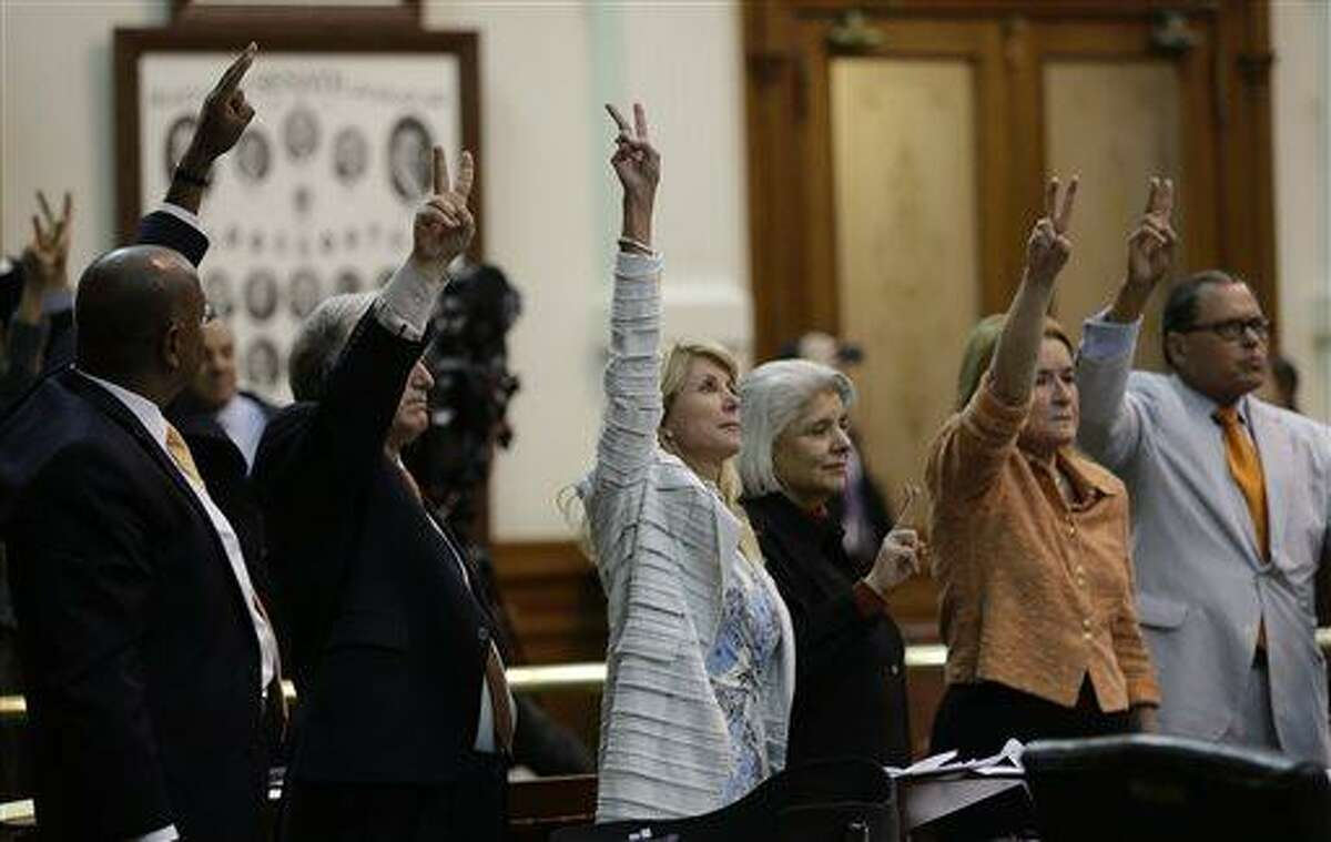 Sen. Wendy Davis, D-Fort Worth, center, who tries to filibuster an abortion bill, hold up a no vote as time expires, Wednesday, June 26, 2013, in Austin, Texas. Amid the deafening roar of abortion rights supporters, Texas Republicans huddled around the Senate podium to pass new abortion restrictions, but whether the vote was cast before or after midnight is in dispute. If signed into law, the measures would close almost every abortion clinic in Texas. (AP Photo/Eric Gay)