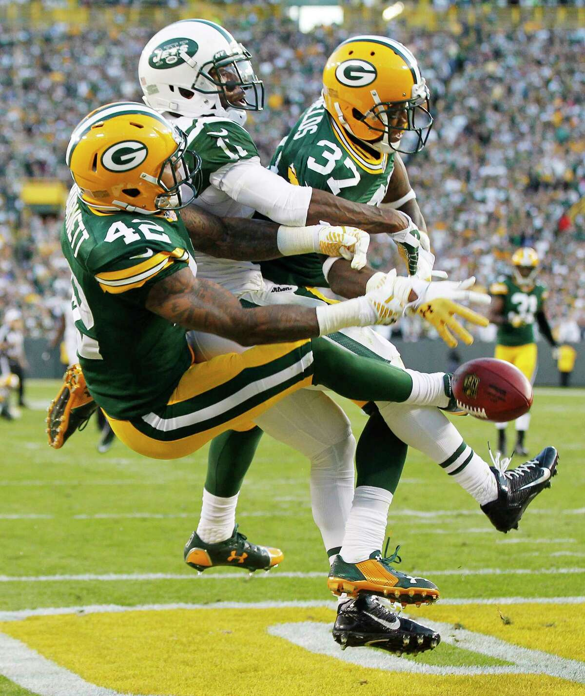 Green Bay Packers' Sam Shields (37) and Morgan Burnett break up a pass intended for New York Jets' Jeremy Kerley during the second half Sunday.