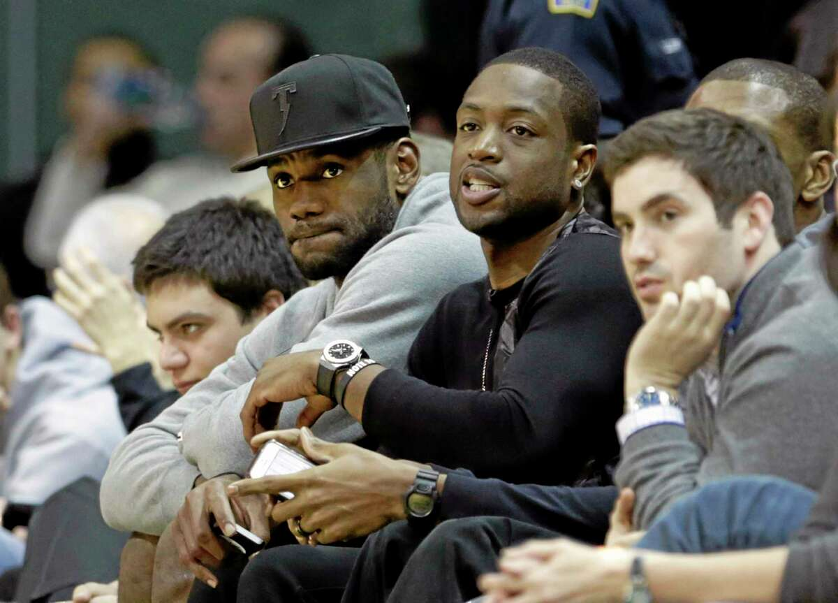 The Miami Heat's LeBron James, left, and Dwyane Wade watch the Duke/Miami game Wednesday night in Coral Gables, Fla. Duke coach Mike Krzyzewski and James will reunite once again to lead USA Basketball.
