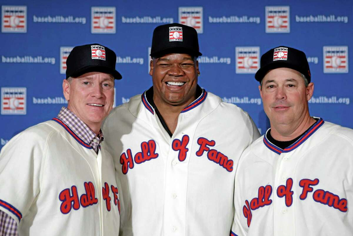 Greg Maddux, right, posing with fellow Hall of Fame inductees Tom Glavine, left, and Frank Thomas, will not have any logo on his cap in his Hall of Fame plaque, the Hall said Thursday. Manager Tony La Russa will also not be associated with one particular team.