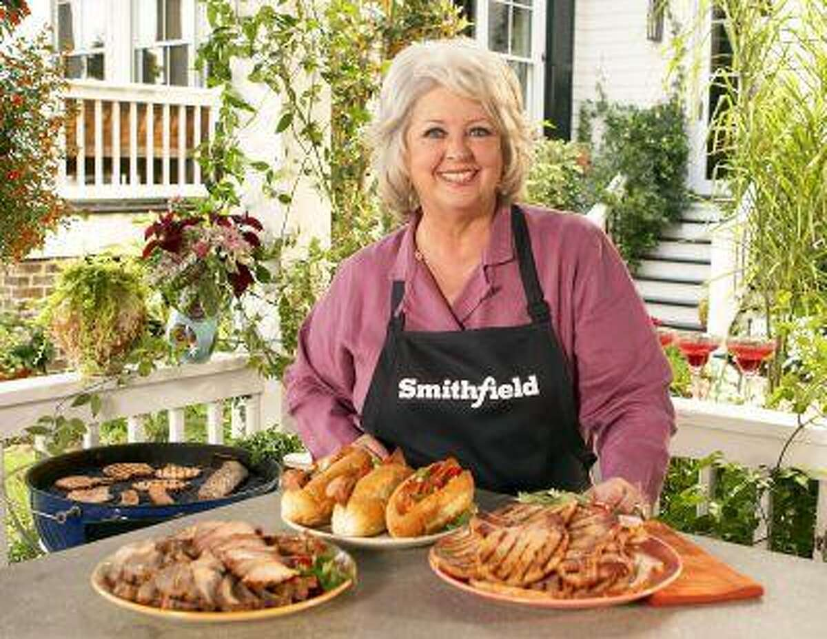 This undated image released by Smithfield Foods shows celebrity chef Paula Deen wearing a Smithfield apron as she stands in front of various Smithfield meat products. On Monday, June 24, 2013, Smithfield Foods said it was dropping Deen as a spokeswoman. The announcement came days after the Food Network said it would not renew the celebrity cook's contract in the wake of revelations that she used racial slurs in the past. (AP Photo/Smithfield Foods via PRNewsFoto)