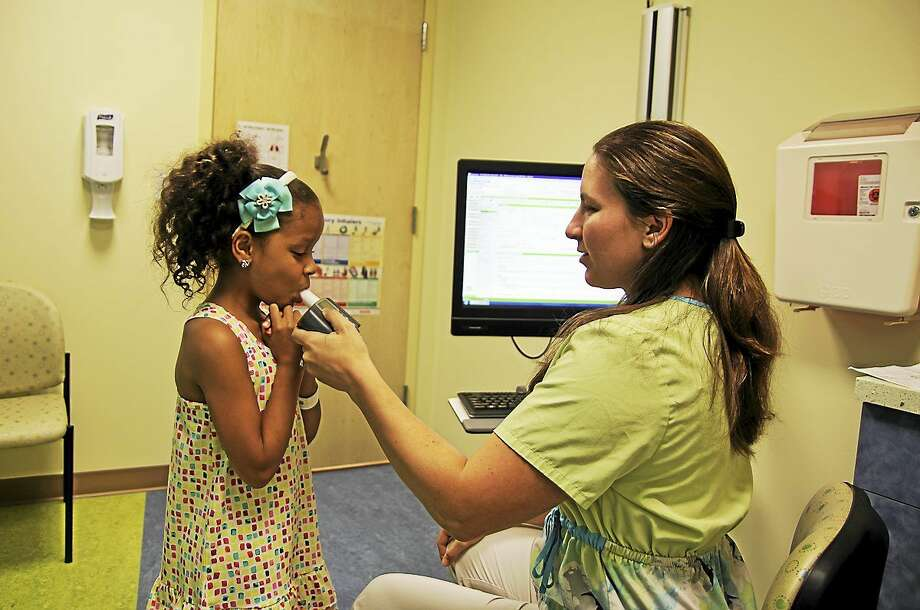 Megan Judkins, a nurse at Dr. Jabob Hen's pediatric pulmonology practice in Trumbull, helps Ariana Gomez, 7, of Ansonia, test her breathing. Photo: (Jodie Mozdzer Gil - Conn. Health I-Team)