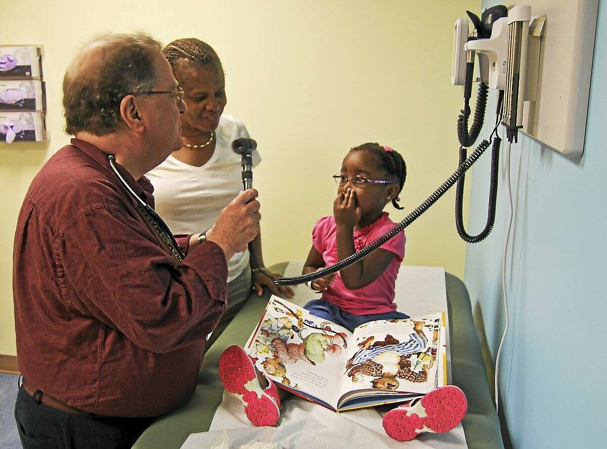 Dr. Jacob Hen talks with Ava Passley, 3, of Bridgeport, in his Trumbull pediatric pulmonology practice recently. Ava's mother, Beverly, looks on.