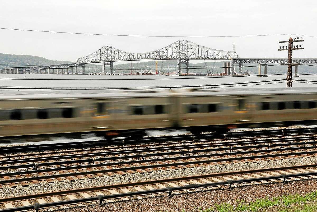 A Metro-North train streaks along the Hudson River just south of the Tappan Zee Bridge in Tarrytown, N.Y.