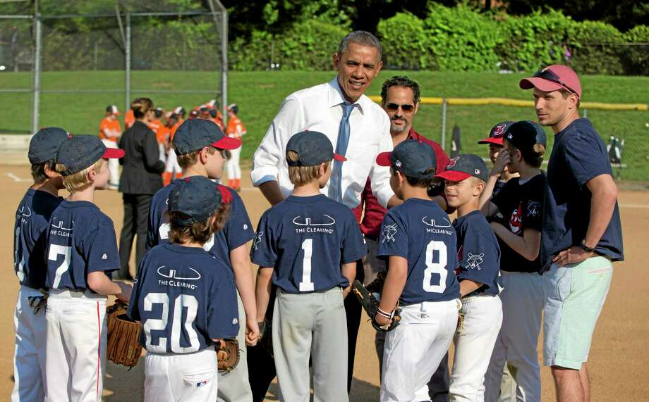President Barack Obama greets players as he makes a unannounced stop to surprise members of the Northwest little league baseball teams at Friendship Park in Washington on Monday. Obama stopped to meet with the players before heading off to a private Democratic fundraiser. Photo: Pablo Martinez Monsivais — The Associated Press  / AP