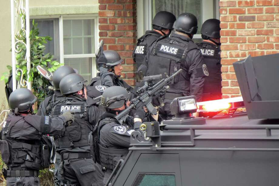 """FILE - In this April 22, 2014, file phot, Nassau County police officers enter a home in Long Beach, N.Y., in search of an armed killer, based on a phone call that turned out to be a hoax. Authorities say the dangerous and costly prank known as ìswatting"""", is becoming increasingly popular among people who play combat games over live video feeds while thousands of people watch. Authorities estimated they spent $100,000 to send more than 60 officers to the Long Beach, Long Island swatting hoax.  (AP Photo/Newsday, Jim Staubitser, File) Photo: AP / Newsday"""