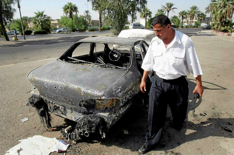 FILE - In this Sept. 25, 2007 file photo, an Iraqi traffic policeman inspects a car destroyed by a Blackwater security detail in al-Nisoor Square in Baghdad, Iraq. The U.S. Justice Department has brought fresh charges against former Blackwater Worldwide security contractors over a deadly 2007 shooting on the streets of Baghdad. The jury indictment announced Thursday, Oct. 17, 2013 charges four men with voluntary manslaughter and other crimes. The case stems from the shooting of 17 Iraqi civilians. Blackwater security contractors were guarding U.S. diplomats when they opened fire at an intersection. Their lawyers have said the insurgents ambushed the guards.  (AP Photo/Khalid Mohammed, File) Photo: AP / AP