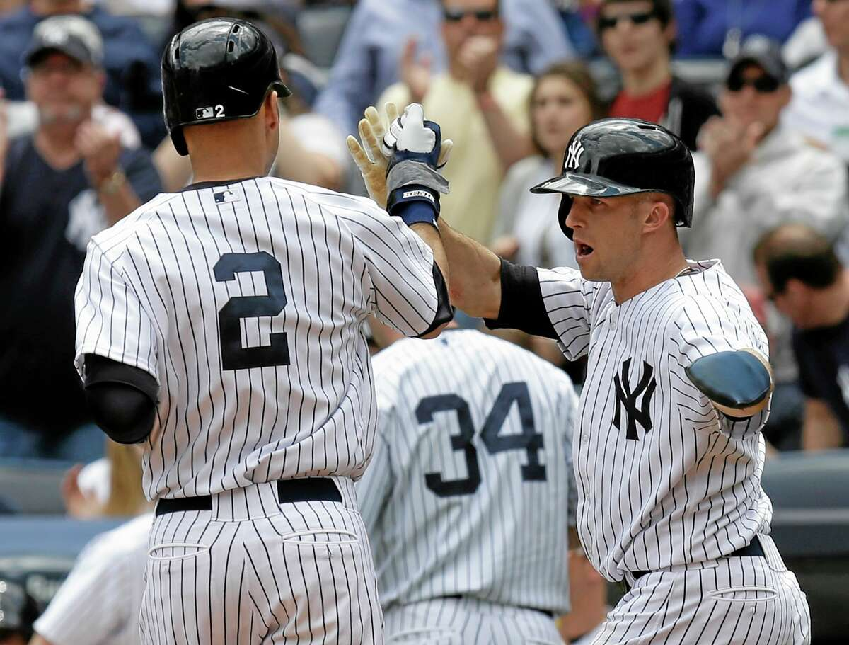 The Yankees' Brett Gardner, right, greets Derek Jeter (2) at home plate after they scored in the first inning of the first game of a doubleheader against the Pirates on Sunday.