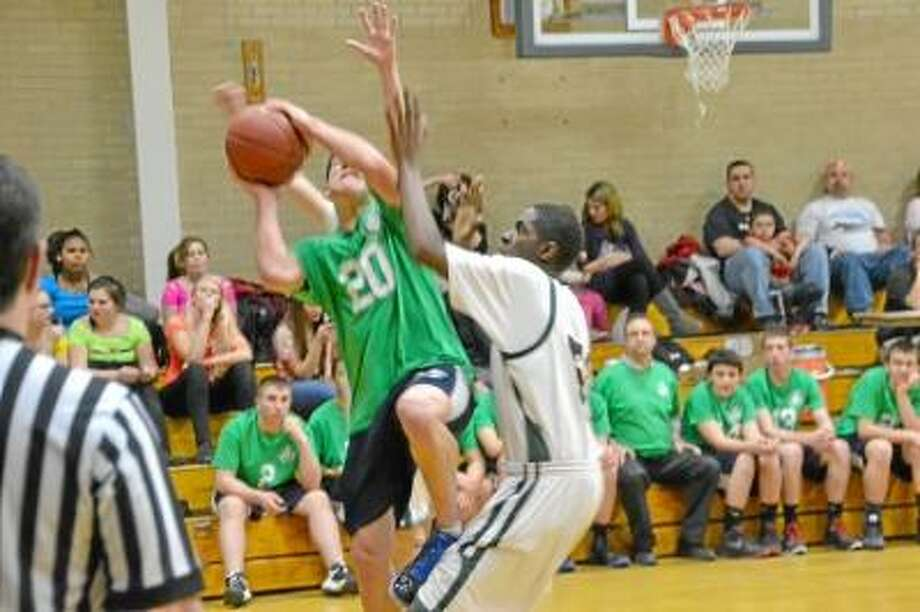Wolcott Tech's Asante Maldon goes up for a layup while being defended by Cheney Tech. Pete Paguaga/Register Citizen