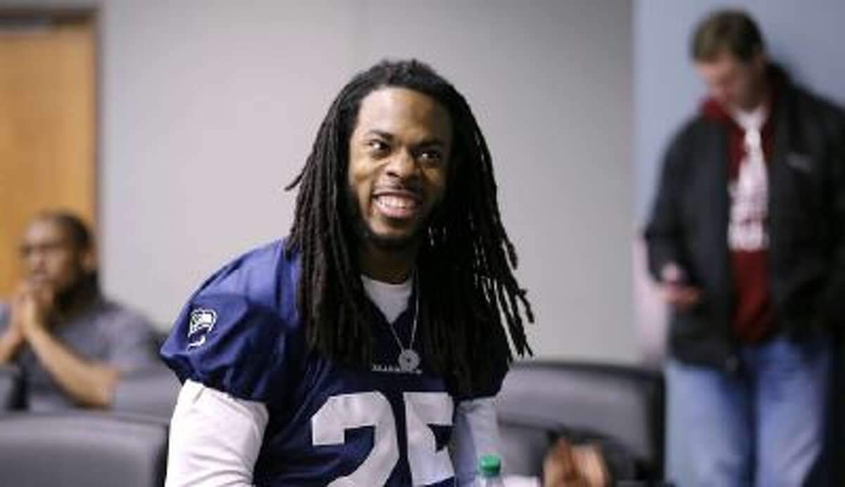 Seattle Seahawks' Richard Sherman smiles as he waits in the back of an interview room for his turn to speak at a press conference.