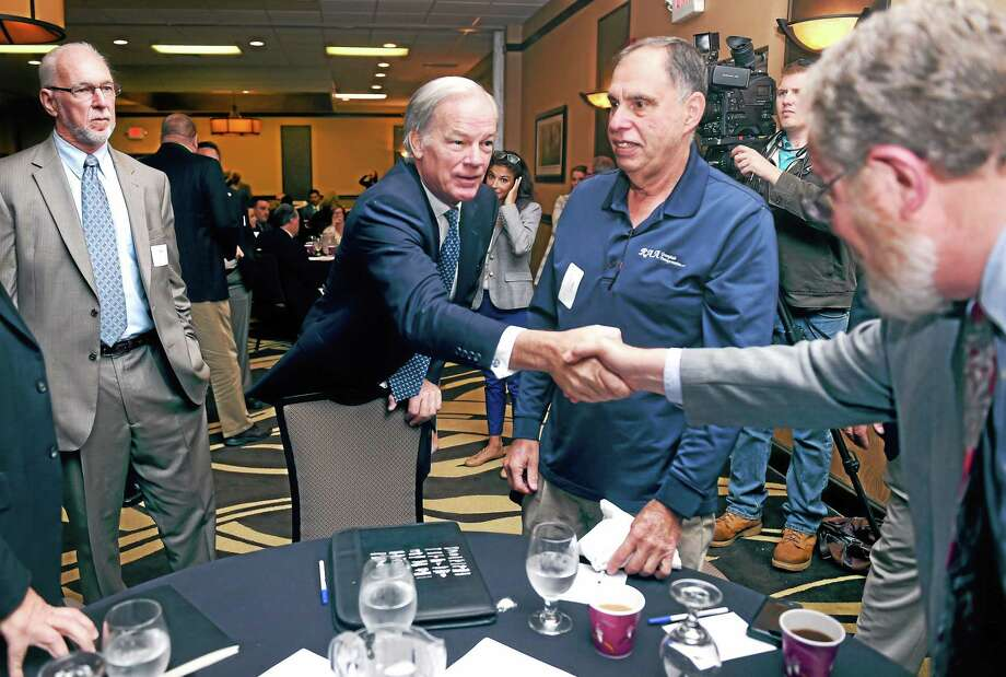 Connecticut gubernatorial candidate Tom Foley, center, shakes hands with John Simone of the CT Main St. Center at a Transportation Forum in North Haven Monday. Photo: Arnold Gold — New Haven Register