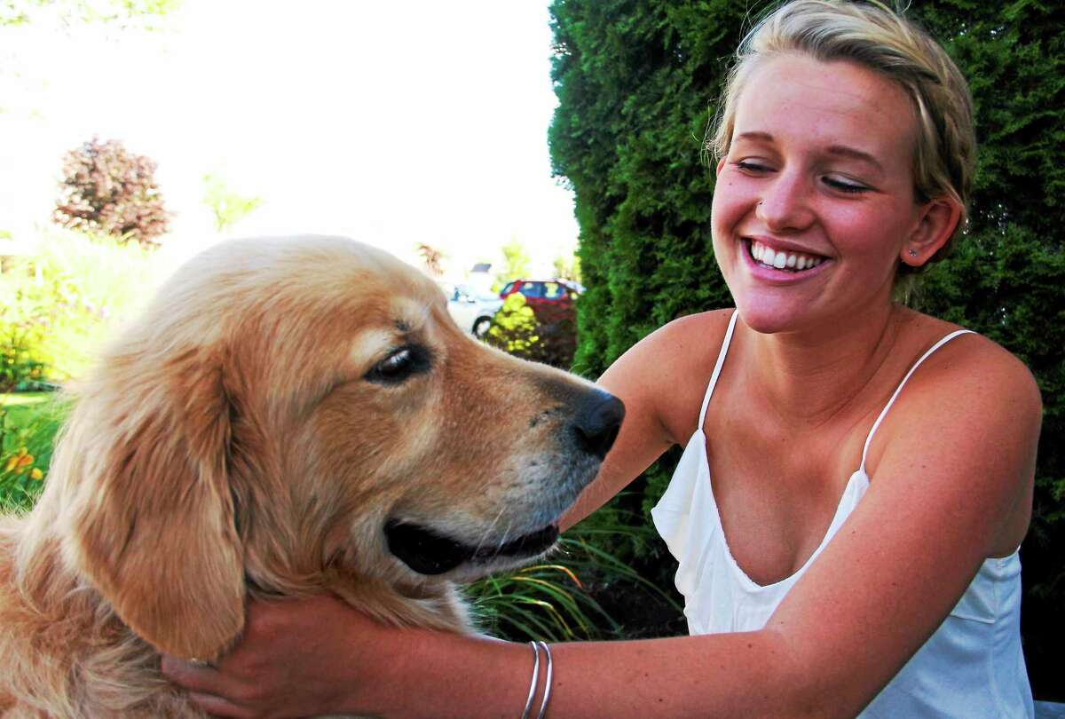 Emmy Fedor, 17, smiles as she pets her dog, Cooper, on Aug. 14 in Torrington. Fedor is an intern at City Hall and is helping develop an ordinance that outlines fees for the regional animal control facility.