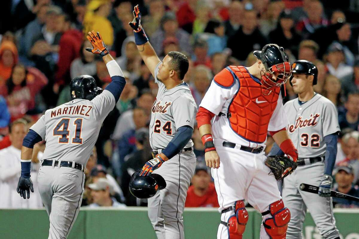 The Tigers' Victor Martinez (41) celebrates his two-run home run that also drove in Miguel Cabrera (24) as Boston Red Sox's A.J. Pierzynski, second from right, looks down, in the third inning Sunday.