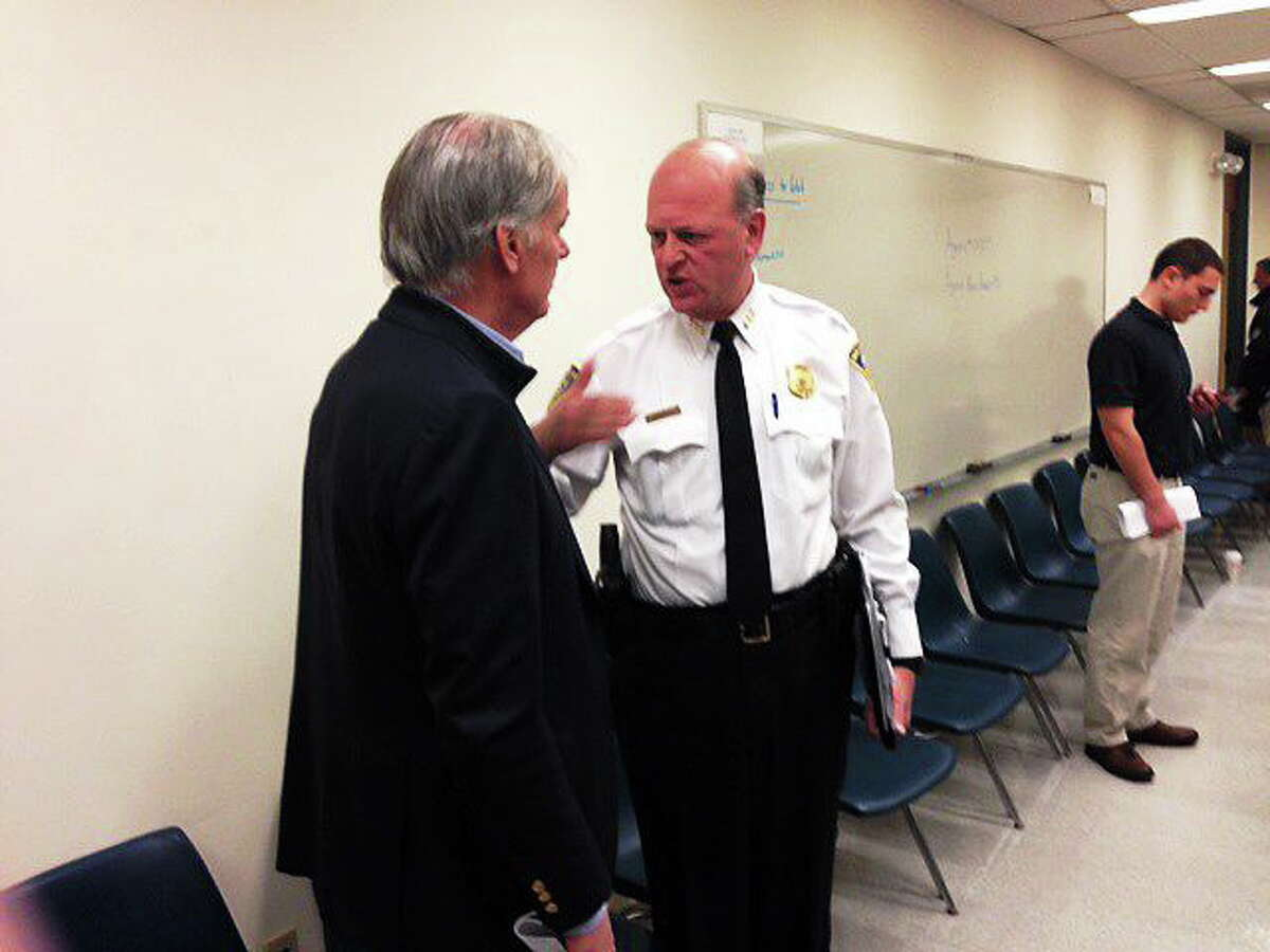 Tom Foley talks to Chief Dean Esserman after the CompStat meeting Thursday. Photo by Rich Scinto/ New Haven Register