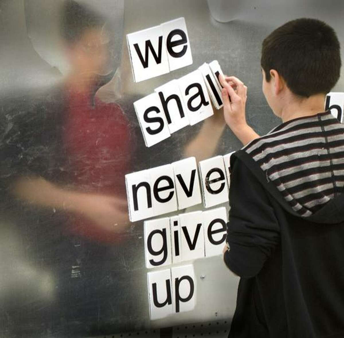 Newtown-Kyle Shelton, 10 of Newtown makes his contribution to the love here now poetry wall at the opening of the Newtown Healing Through The Arts Center. Melanie Styengel/Register