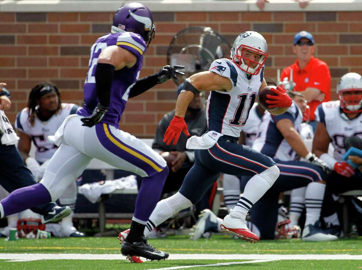 Patriots wide receiver Julian Edelman, right, runs with the ball past Vikings free safety Harrison Smith after catching a pass during the second quarter Sunday.