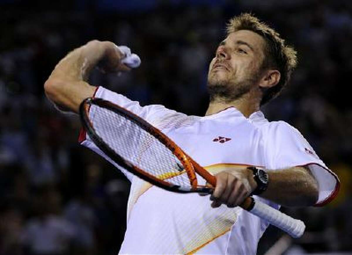 Stanislas Wawrinka of Switzerland throws his wristband to the spectators after defeating Tomas Berdych of the Czech Republic during their semifinal at the Australian Open tennis championship in Melbourne, Australia, Thursday, Jan. 23, 2014.