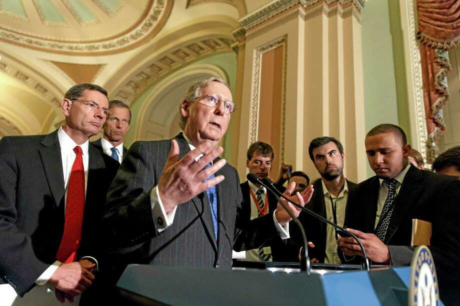 Senate Minority Leader Mitch McConnell, R-Ky., joined by Sen. John Barrasso, R-Wyo., left, and Sen. John Thune, R-S.D., rear left, speaks to reporters after a Republican caucus meeting, at the Capitol in Washington, Tuesday, May 6, 2014. (AP Photo/J. Scott Applewhite) Photo: AP / AP