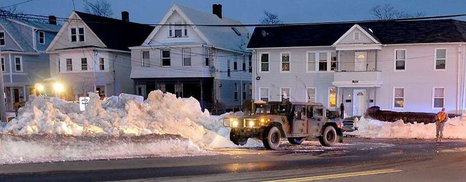 Pennsylvania Air National Guard from the 201st Red Horse Unit and the 228 BSB based in Fort Indiantown Gap in Pennsylvania set up a road block so their team can work with heavy equipment and shovels Wednesday February 13, 2013 clearing out Blizzard 2013 snow on  Plymouth Street in New Haven, Connecticut New Haven, Connecticut.   Photo by Peter Hvizdak / New Haven Register Photo: New Haven Register / ©Peter Hvizdak /  New Haven Register