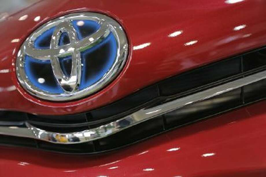 In this Aug. 2, 2013 file photo, the emblem of a Toyota car shines at Toyota Motor Corp.'s showroom Toyota Mega Web in Tokyo. Toyota remained the top-selling automaker for a second year in a row, beating U.S. rival General Motors by some 270,000 vehicles in 2013, and set an ambitious target to sell more than 10 million vehicles in 2014. That would mark a milestone as no automaker has ever topped annual worldwide sales of 10 million.
