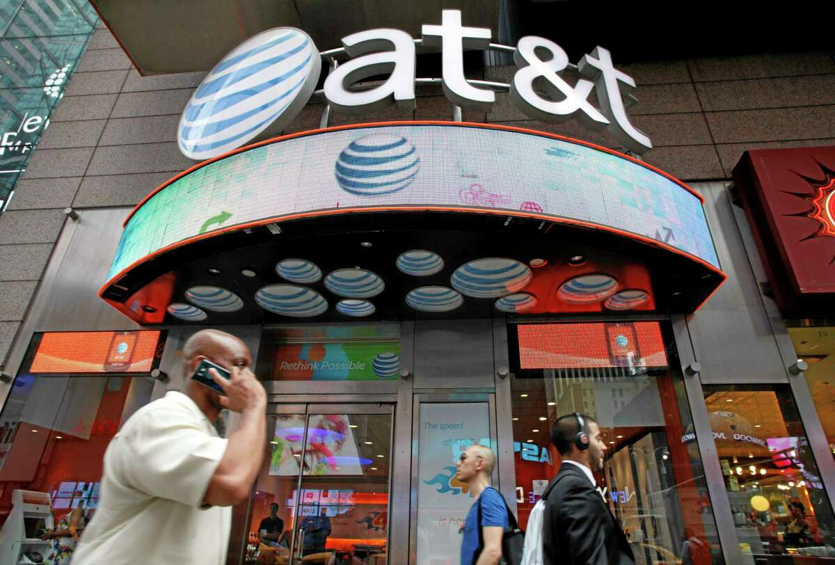 FILE - In this July 11, 2013 photo, a man uses a cell phone as he walks past an AT&T store in New York. (AP Photo/Mark Lennihan, File)