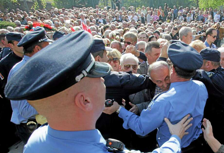 Serbian police try to contain the admiring crowds that throng the funeral of Tito's widow in Belgrade, Serbia, Saturday. (Photo AP/Darko Vojinovic) Photo: AP / AP