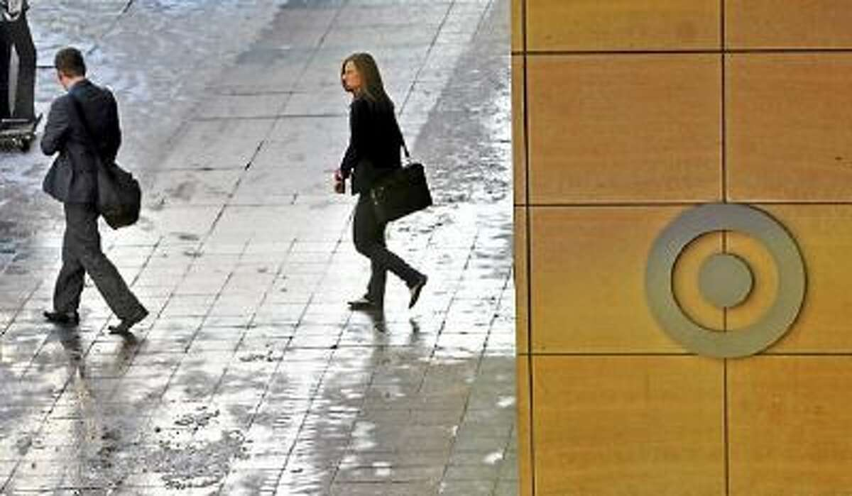 People walk out of the Target headquarters in downtown Minneapolis Wednesday. The company announced it is laying off 475 employees.