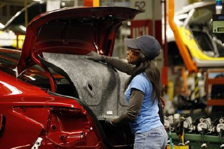 A Nissan employee tacks in the trunk lining into an new Altima sedan chassis Thursday, Jan. 10, 2013 at its Canton, Miss., manufacturing plant. Photo: AP / AP2013