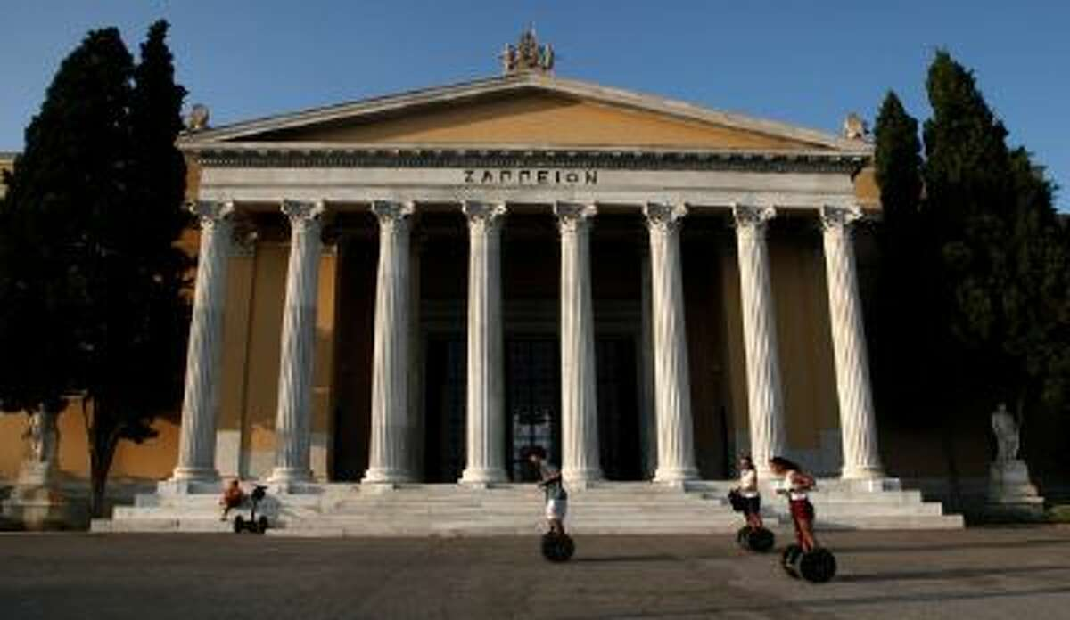 Tourists enjoy a ride on segways in front of the Zappeio convention hall in Athens.