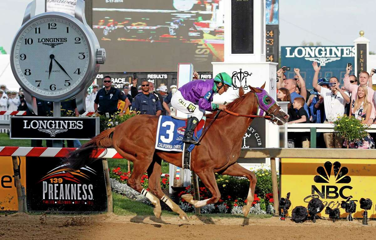 California Chrome, ridden by jockey Victor Espinoza, wins the 139th Preakness Stakes at Pimlico Race Course on Saturday in Baltimore.