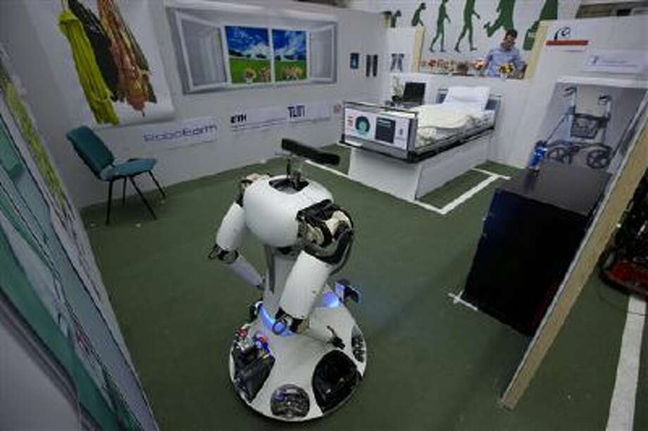 Amigo, a white robot the size of a person, uses information gathered by other robots to move toward a table to pick up a carton of milk and deliver it to an imaginary patient in a mock hospital room at the Technical University of Eindhoven, Netherlands. Photo: AP / AP