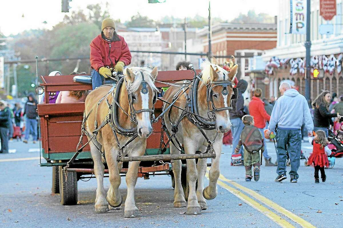 A team of horses from Bunnell Farm gives rides down Main St. in Torrington during the city's Trunk-or-Treak event on Saturday.Lauri Gaboardi - Register Citizen