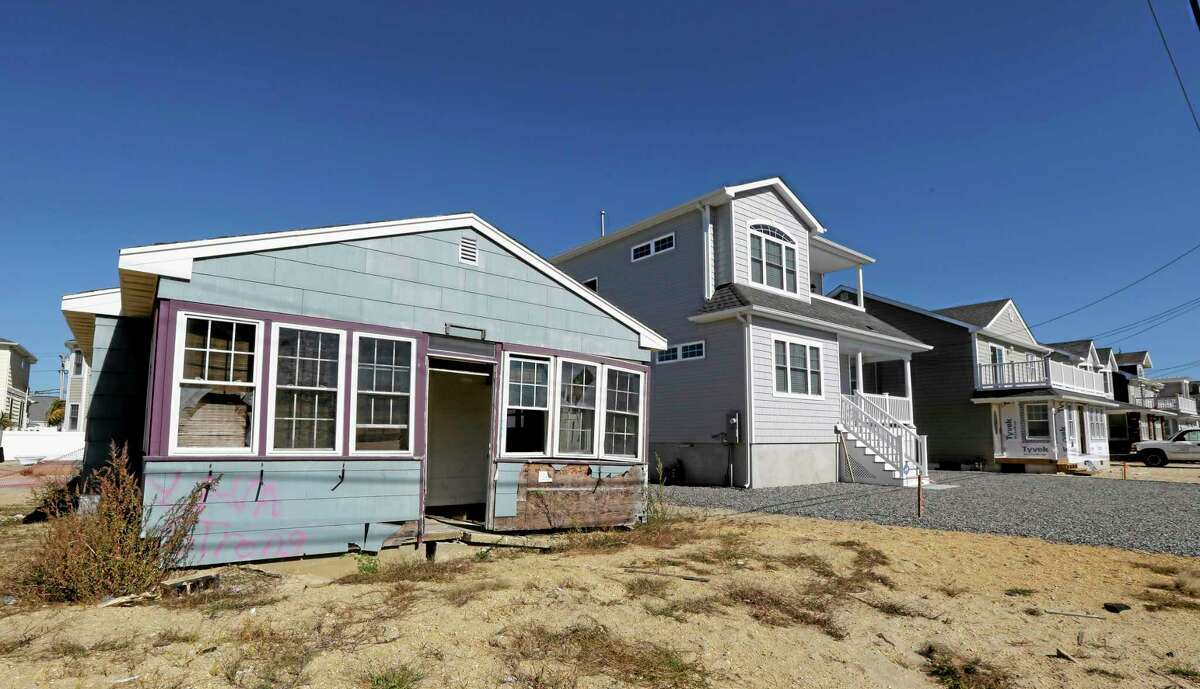 This Friday, Oct. 18, 2013 photo shows the vacation home of Cora Hoch, left, in Lavallette, N.J. The home, which was damaged by Superstorm Sandy, has been gutted and no repairs have been made to it while neighbor homes are up and running again.