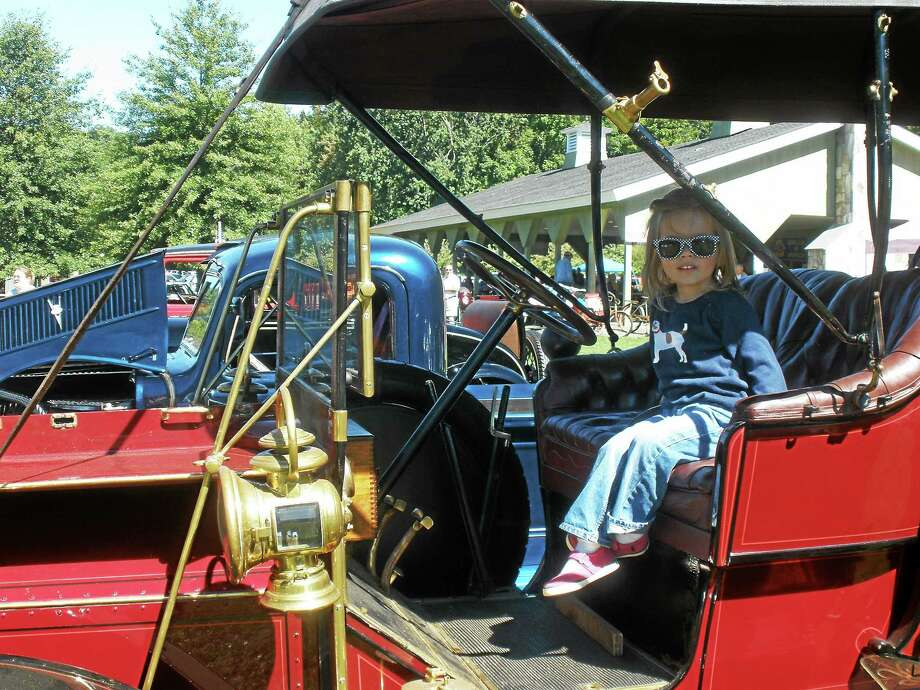 A young visitor checks out the interior of a vintage car entered in the Car-B-Que at Washington Depot's River Walk pavilion. The event, a fundraiser for the town's Lions Club, ambulance association and scholarship funds, is held in memory of resident Jim Bennett and his wife Fran. Photo: Stephen Underwood — Register Citizen