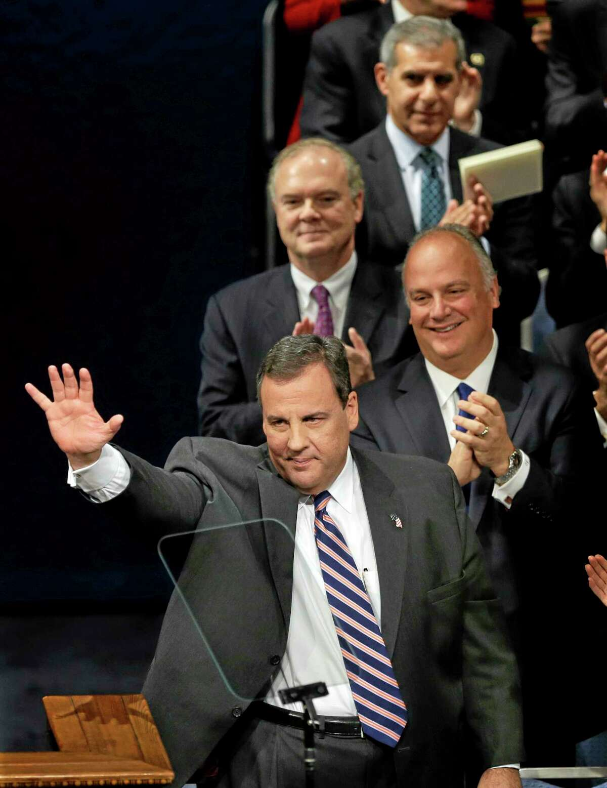 In this photograph taken Tuesday, Jan. 21, 2014, as his brother Todd Christie, right, Bob Martin, back left, Commissioner of the New Jersey Department of Environmental Protection and New Jersey Sen. Joseph M. Kyrillos, Jr., R-Middletown, look on, New Jersey Gov. Chris Christie waves to a gathering after being sworn in for his second term in Trenton, N.J. Two recent polls show a traffic jam scandal taking a toll on Gov. Chris Christie's popularity and national political ambitions. A Rutgers-Eagleton poll released Wednesday, Jan. 22, 2014, shows the governor's job performance and approval rating dipping. And a Quinnipiac University poll released Tuesday found a third of respondents less likely to vote for Christie for president. (AP Photo/Mel Evans)