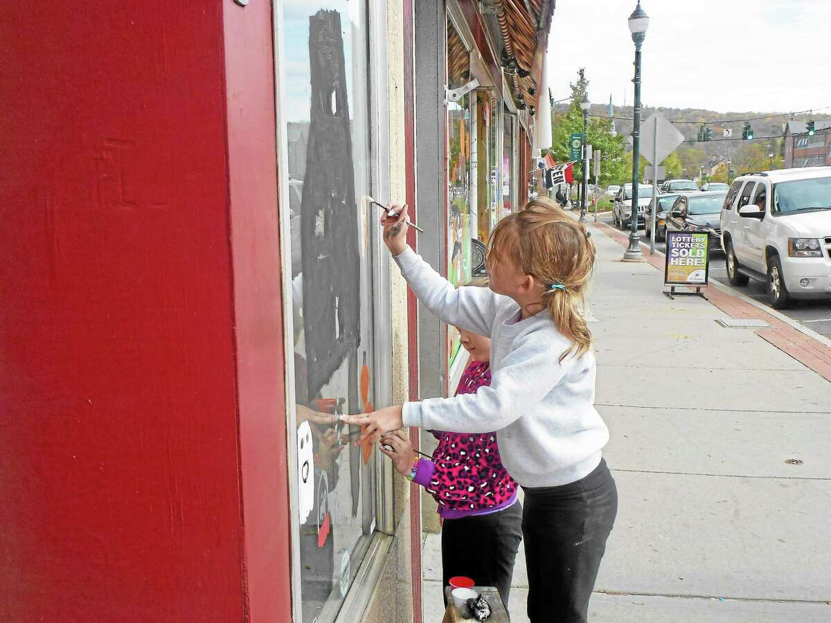 Ryan Flynn - Register CitizenChildren like Angela Bardino and Kaitlyn Crowley painted the windows of local businesses, adding a Halloween theme to much of Main Street.