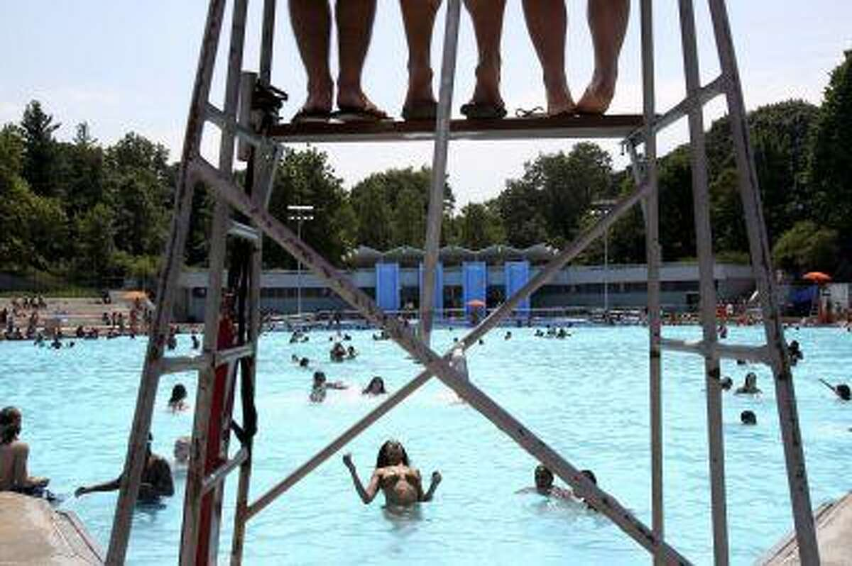 Lifeguards, top, watch over swimmers at Lasker Pool in New York, Thursday, June 28, 2012. The city's 55 outdoor pools opened to the public for the season on Thursday. (AP Photo/Seth Wenig)