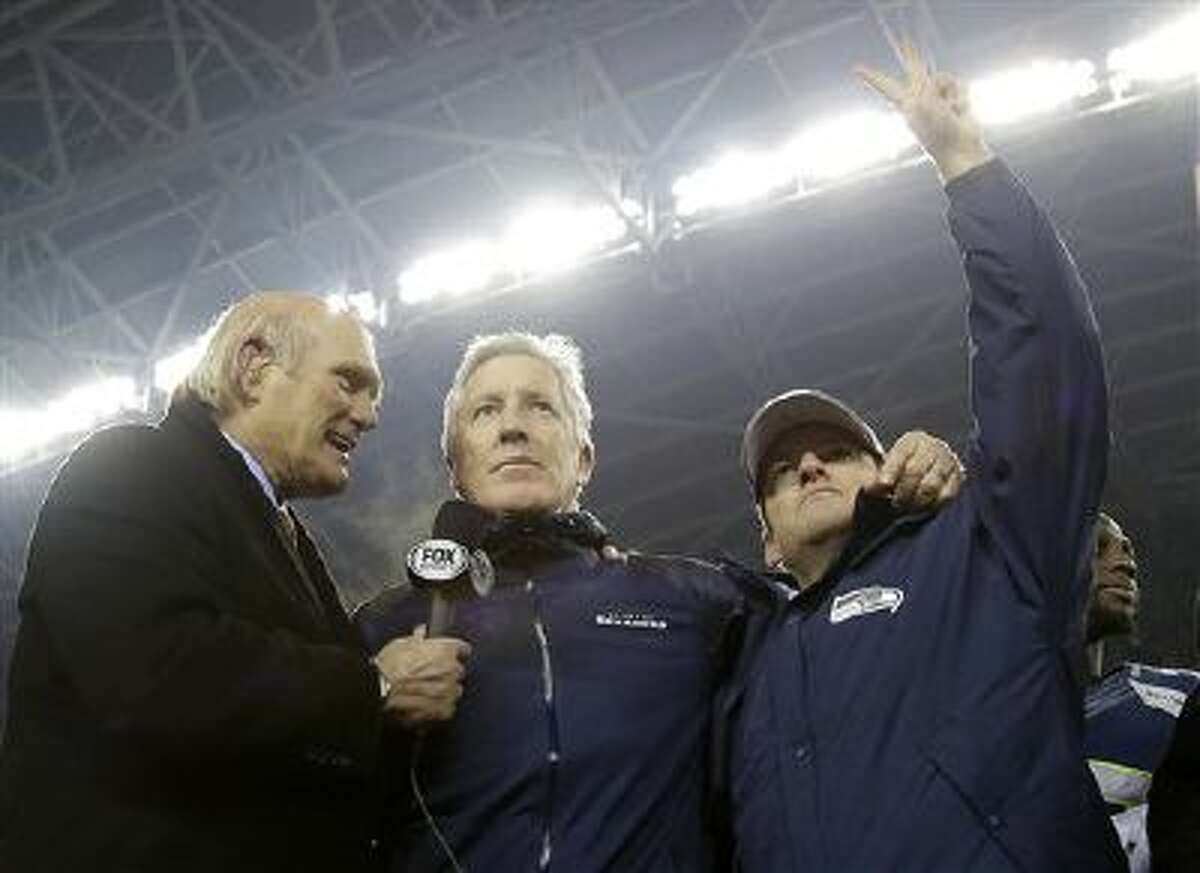 Former NFL player and sports broadcast host Terry Bradshaw interviews Seattle Seahawks head coach Pete Carroll as Seattle Seahawks owner Paul Allen waves after the NFL football NFC Championship game against the San Francisco 49ers Sunday, Jan. 19, 2014, in Seattle. The Seahawks won 23-17 to advance to Super Bowl XLVIII.