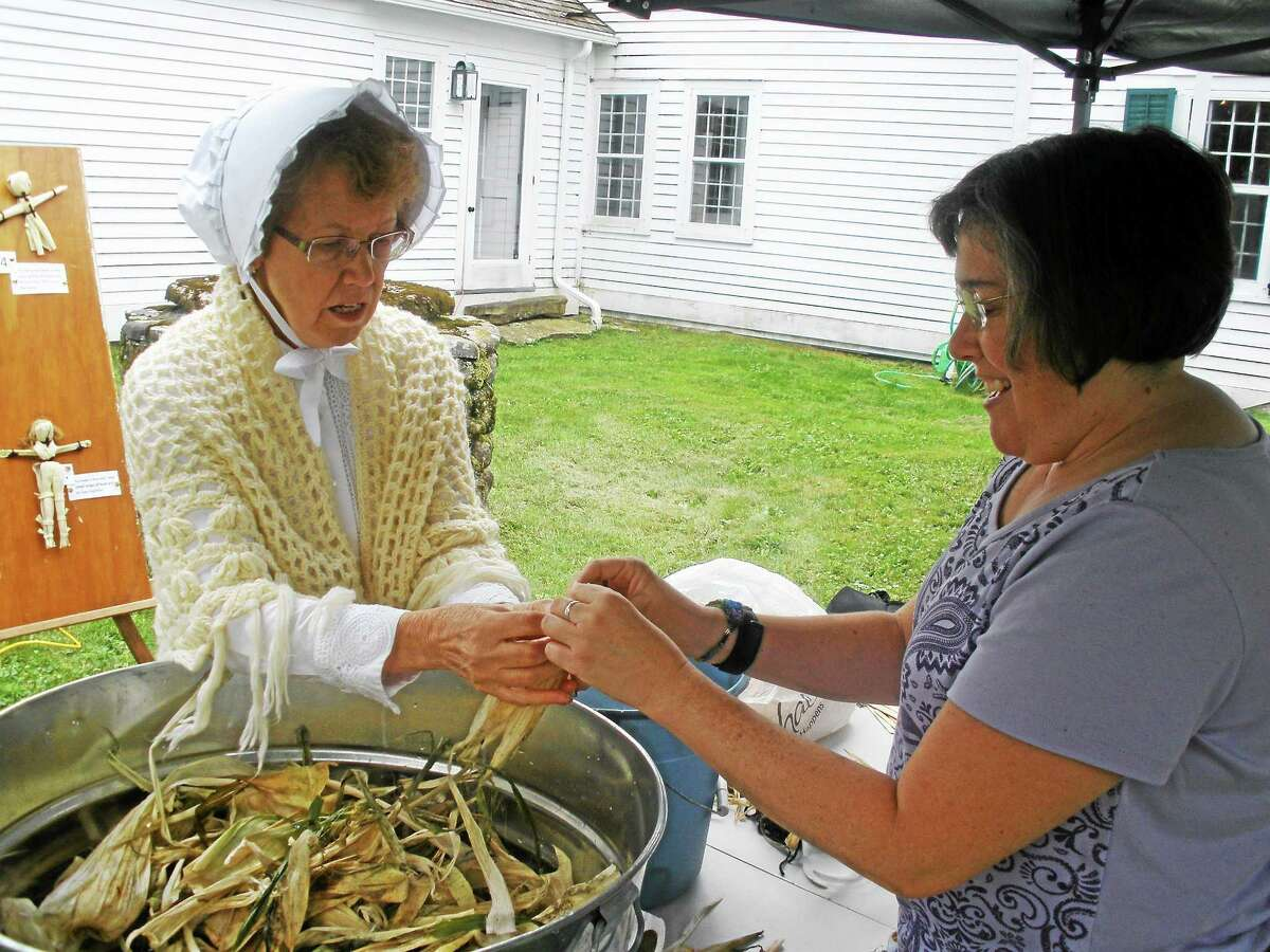 Stephen Underwood/Register Citizen A visitor to Old Barkhamsted Day learns the art of making a corn husk doll.