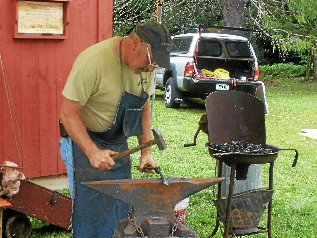 Stephen Underwood/Register Citizen Blacksmith Robert Valentine, who is also Goshen's First Selectman, demonstrates his skills during Old Barkhamsted Day on Sunday.