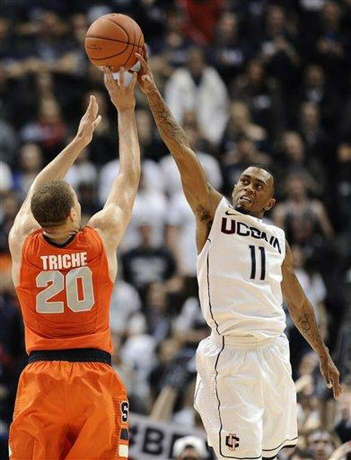 Connecticut's Ryan Boatright, right, blocks a shot-attempt by Syracuse's Brandon Triche in the final minutes of second half of an NCAA college basketball game in Hartford, Conn., Wednesday, Feb. 13, 2013. Connecticut won 66-58. (AP Photo/Jessica Hill) Photo: ASSOCIATED PRESS / A2013