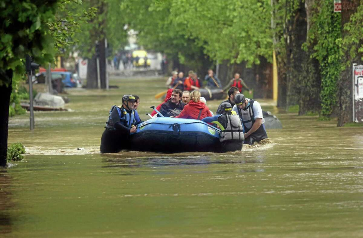 Members of the Bosnian Army rescue people from their flooded homes, in the Bosnian town of Maglaj, 150 kms north of Sarajevo, Friday May 16, 2014. Two people drowned in Serbia and the country declared a national emergency Thursday as rain-swollen rivers across the Balkans flooded roads and bridges, shut down schools and cut off power. Hundreds of people had to be evacuated. In Serbia and neighboring Bosnia, meteorologists said the rainfall was the most since measuring started 120 years ago. Belgrade authorities say the average rainfall of a two-month period hit the city in just 40 hours. (AP Photo/Amel Emric)