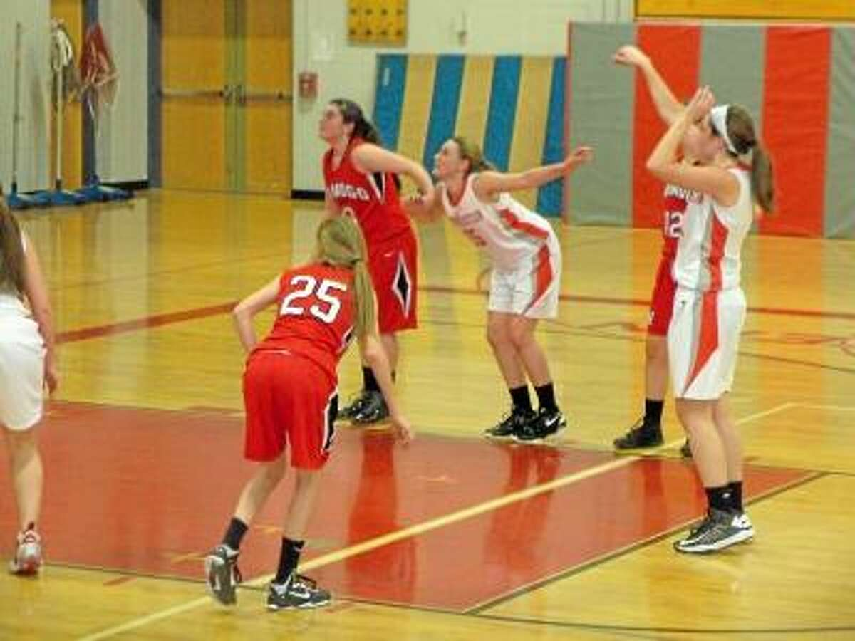 Northwestern sophomore Emma Beltrandi shoots a foul shot as tammate Arielle Oemcke and Wamogo's JennoPardo and Brooke Neller (No. 25) look for a rebound. Pete Wallace/Register Citizen