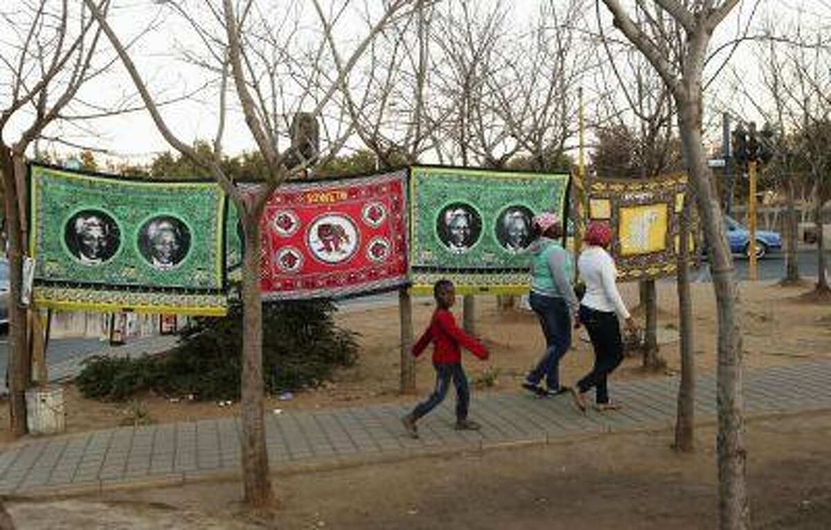 People walk past banners of former South African President Nelson Mandela, in Soweto June 24, 2013. (Siphiwe Sibeko/Reuters)