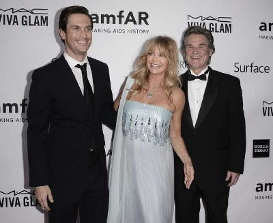 From left to right, actor Oliver Hudson, actress and honoree Goldie Hawn, and husband, actor Kurt Russell arrive at the fourth annual amfAR Inspiration Gala at Milk Studios on Thursday, Dec. 12, 2013 in Los Angeles.