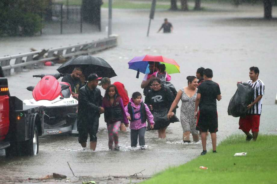 Families cross a flooded bridge near White Oak Bayou, Sunday, Aug. 27,
