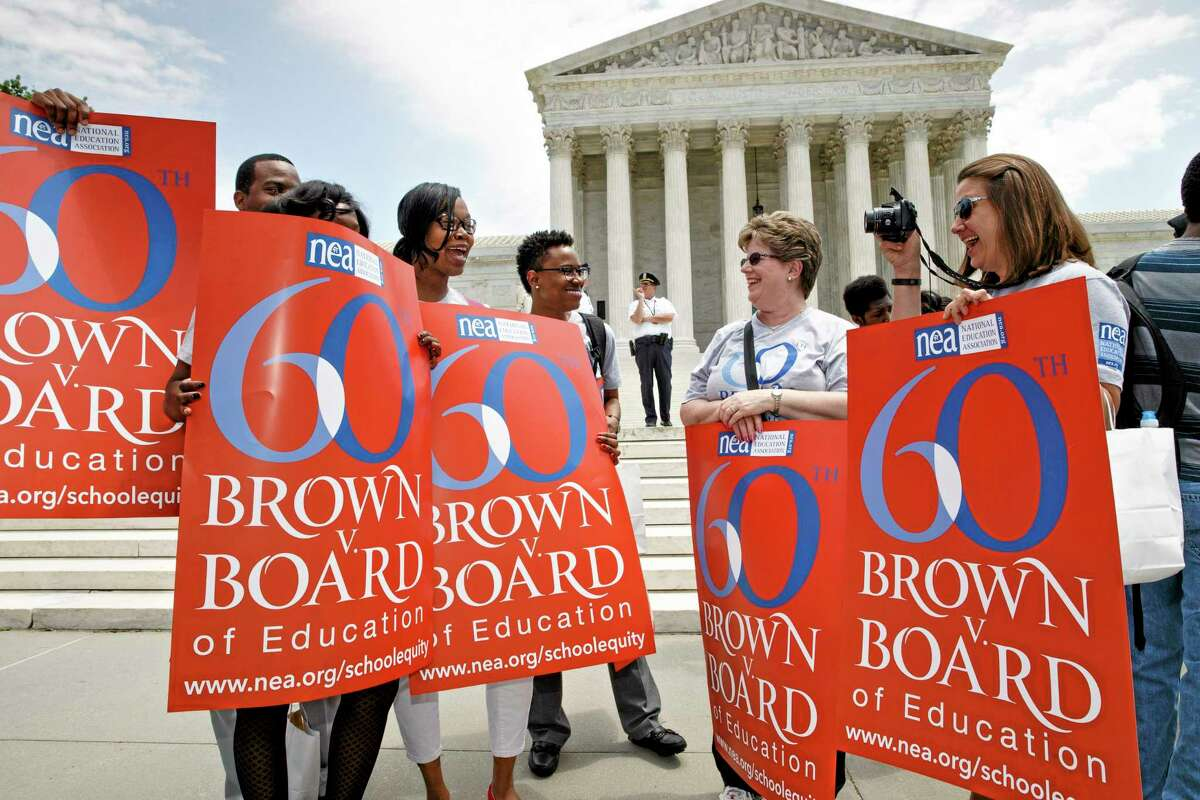 This photo taken May 13, 2014 ,shows National Education Association staff members from Washington joining students, parents and educators at a rally at the Supreme Court in Washington on the 60th anniversary Brown v. Board of Education decision that struck down ìseparate but equalî laws that kept schools segregated. Saturday marks the 60th anniversary of the landmark Brown v. Board of Education decision. Many inequities in education still exist for black students and for Hispanics, a population that has grown exponentially since the 1954 ruling.