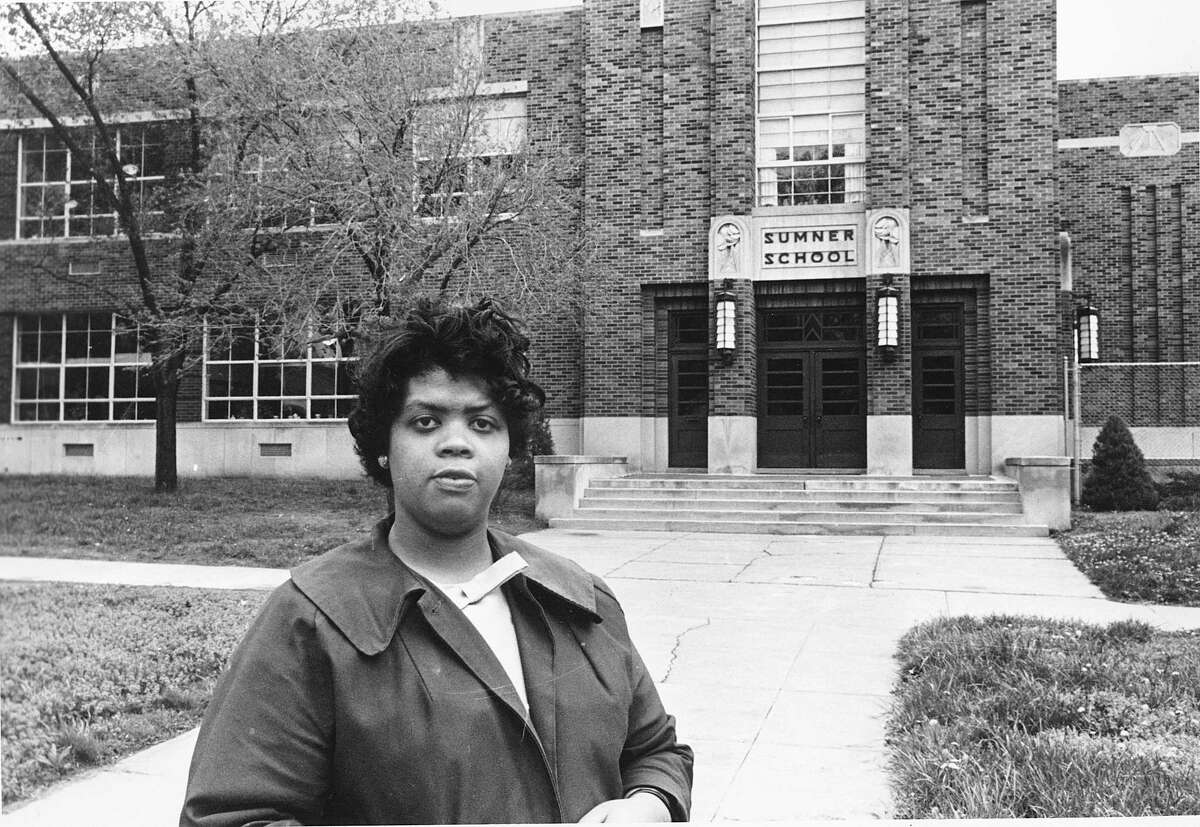 """This May 8, 1964 file photo shows Linda Brown Smith standing in front of the Sumner School in Topeka, Kansas. The refusal of the public school to admit Brown in 1951, then nine years old, because she is black, led to the Brown v. Board of Education of Topeka, Kansas. In 1954, the U.S. Supreme Court overruled the """"separate but equal"""" clause and mandated that schools nationwide must be desegregated. Saturday marks the 60th anniversary of the landmark Brown v. Board of Education decision. Many inequities in education still exist for black students and for Hispanics, a population that has grown exponentially since the 1954 ruling."""
