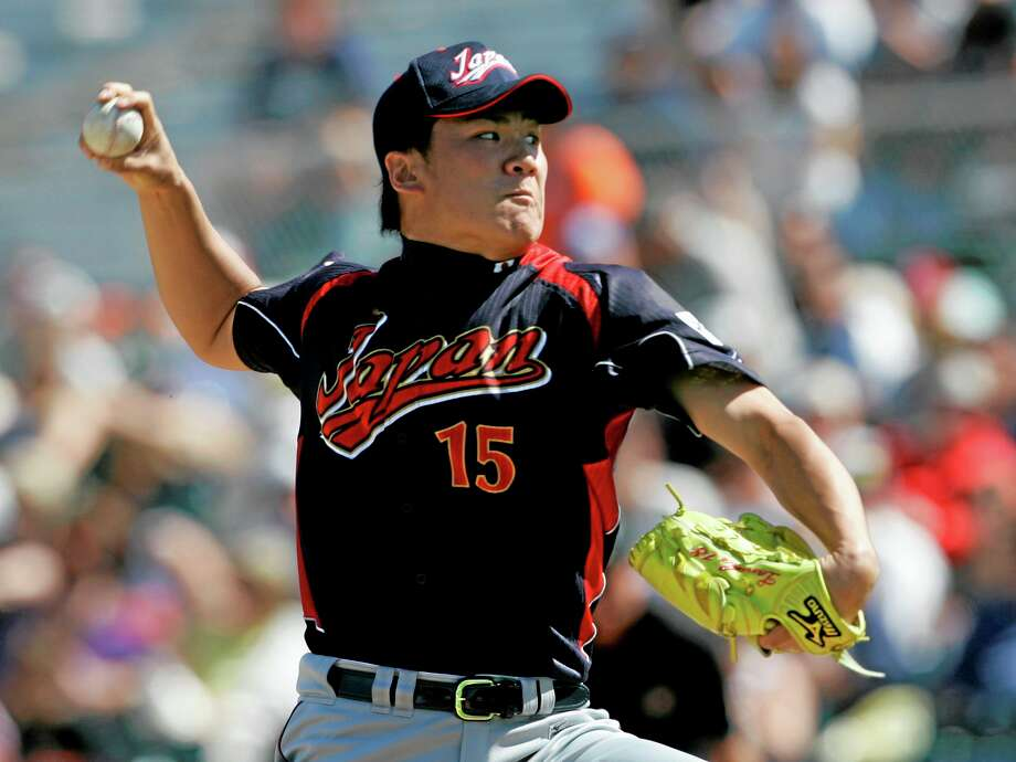 In this March 11, 2009, file photo, Japan's Masahiro Tanaka pitches to the San Francisco Giants during an exhibition game in Scottsdale, Ariz. The New York Yankees and Tanaka agreed on Wednesday to a $155 million, seven-year contract. In addition to the deal with the pitcher, the Yankees must pay a $20 million fee to the Japanese team of the 25-year-old right-hander, the Rakuten Golden Eagles. Photo: Jeff Chiu — The Associated Press  / AP